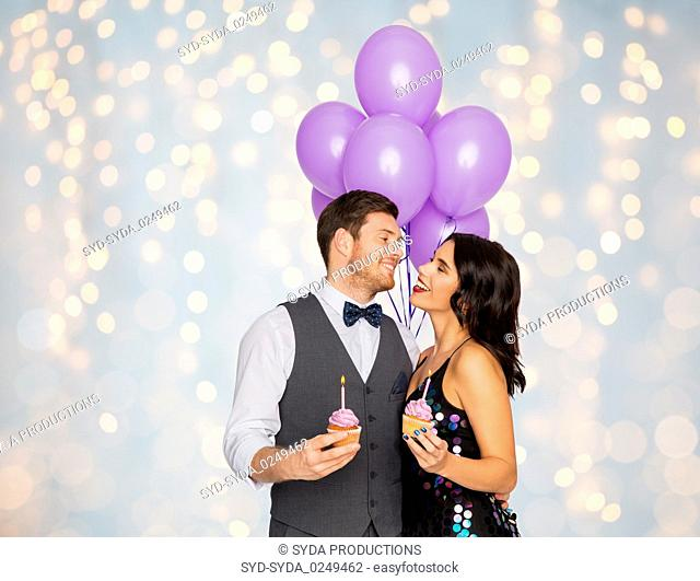 happy couple with balloons and cupcakes at party