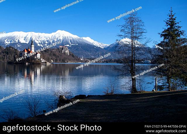 15 February 2021, Slovenia, Bled: The Church of the Assumption of the Virgin Mary on the island of Blejski Otok in Lake Bled at the foot of the Pokljuka plateau