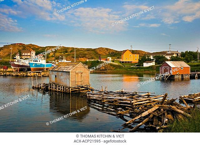 Fishing shack with wharf made from rough cut spruce in foreground and boats at harbour in background in the fishing village of Durrell