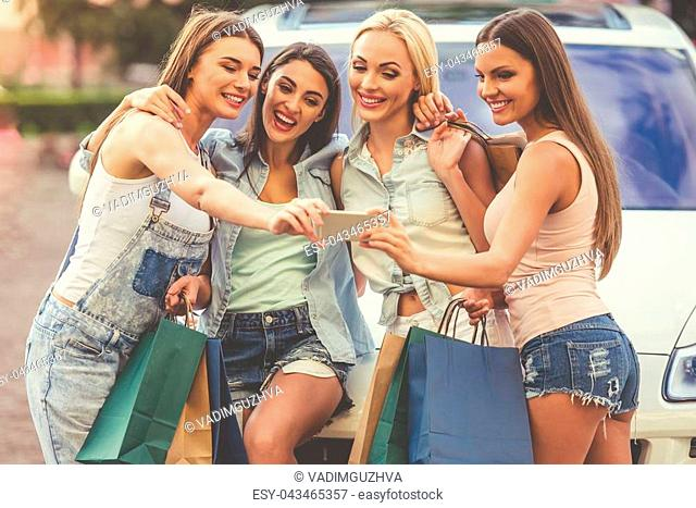 Beautiful stylish girls are holding shopping bags, making selfie using a smart phone and smiling while leaning on their car outdoors