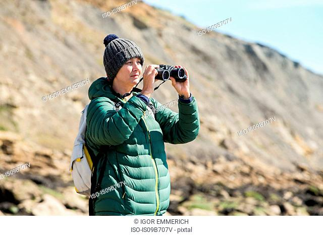 Woman using binoculars on rock, Folkestone, UK
