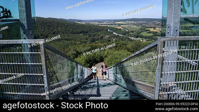 05 August 2020, Lower Saxony, Rinteln: A couple leaves the lookout point Jahrtausendblick at the former leisure park Steinzeichen Steinbergen in the district of...