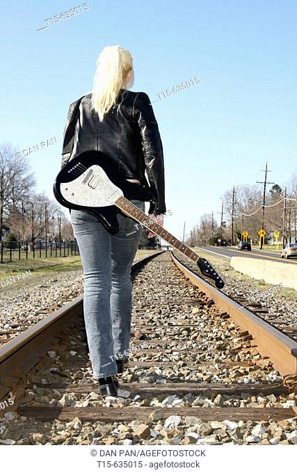 Young woman carrying a guitar standing on railroads looking into and thinking about future