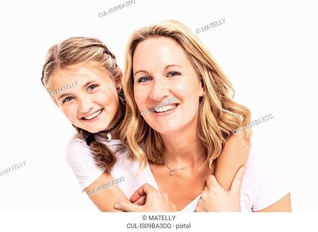 Studio portrait of girl with arms around her mother, head and shoulders