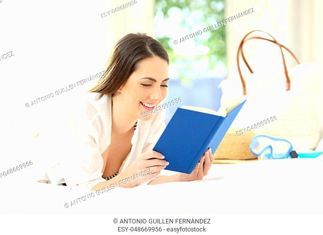 Happy woman reading a book lying on the bed in an hotel room on summer vacations
