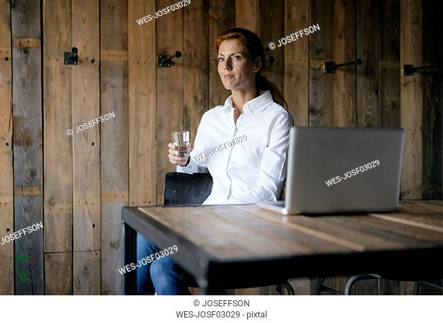 Businesswoman sitting at desk with glass of water and laptop
