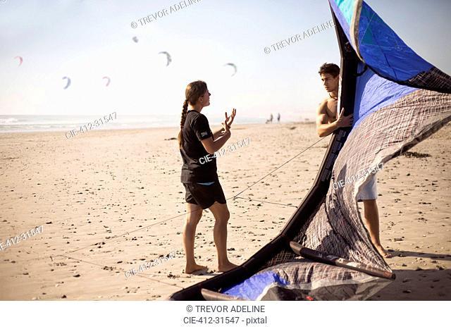 Woman instructing man with kiteboarding kite on sunny beach
