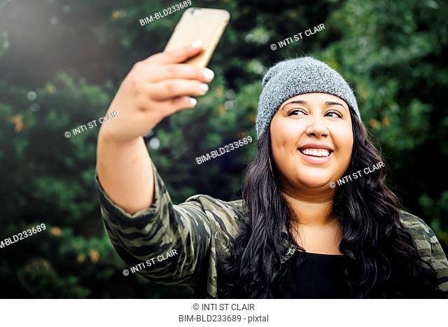 Mixed Race woman posing for cell phone selfie in forest