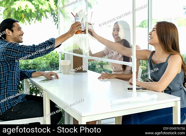 Asian customers cheers and celebrating social distancing in restaurant. New normal lifestyle in food and drink concept