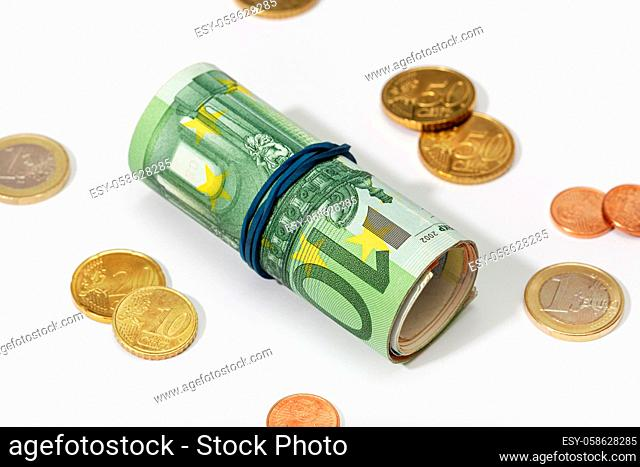 Roll of euro bills with rubber band and coins isolated on white background. Money concept
