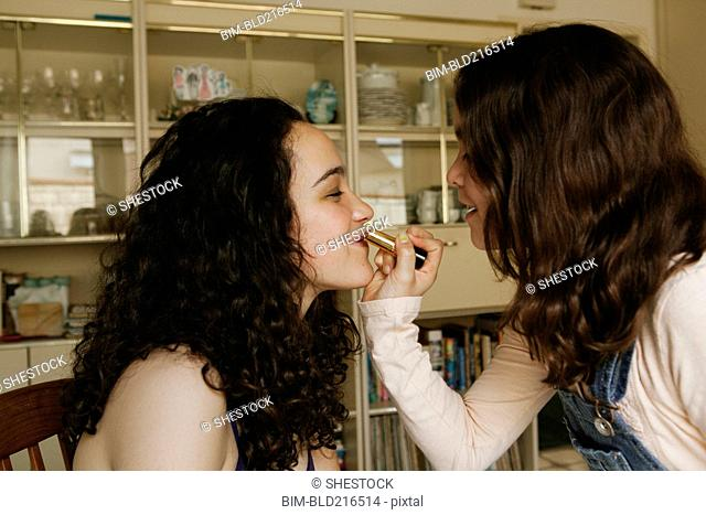 Girl applying lipstick on sister