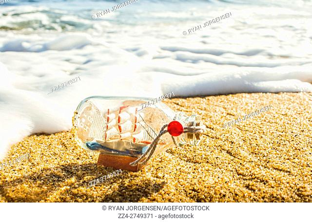 Marine theme landscape of a wooded small boat inside bottle on surf sand at beach. Tide of conquest