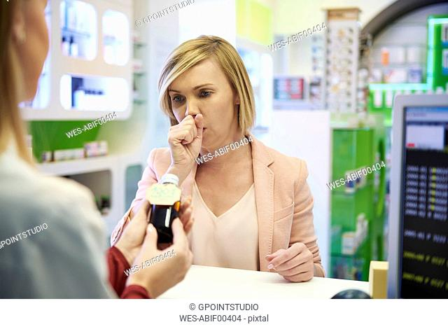 Pharmacist selling cough syrup to woman in pharmacy