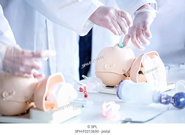Doctors practising infant intubation