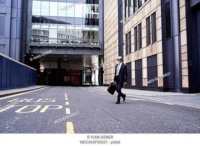 UK, London, senior businessman with headphones crossing the street