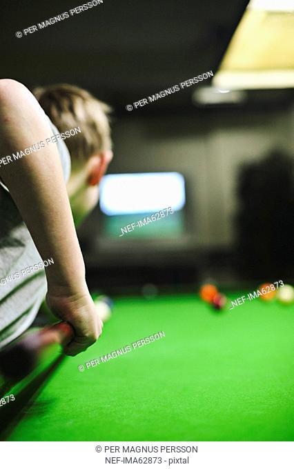 A boy playing pool