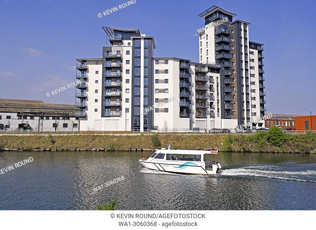 Cardiff Bay Aquabus and modern riverside residential block on the river Taff, Wales UK