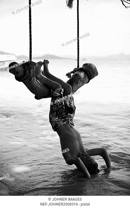 Boy swinging above sea