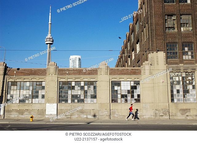 Toronto Canada: jogging along a deserted sidewalk, the CN Tower on the background