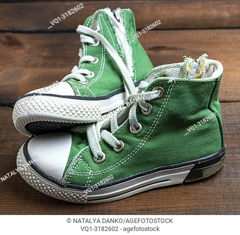 very old pair of worn green textile sneakers