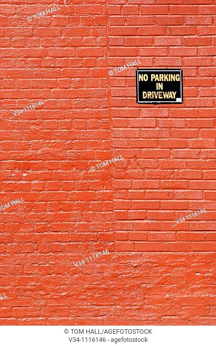 Red brick wall with no parking sign