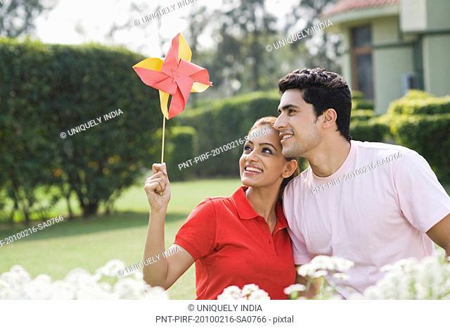 Couple looking at a pinwheel and smiling
