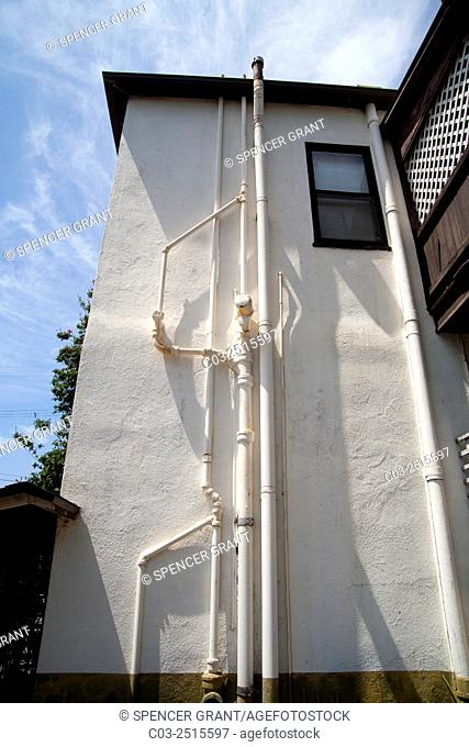 A complex system of external pipes serves the plumbing needs of an old stucco apartment building in Long Beach, CA