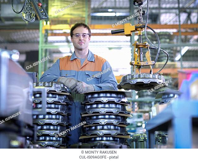 Portrait of worker on production line in industrial clutch factory
