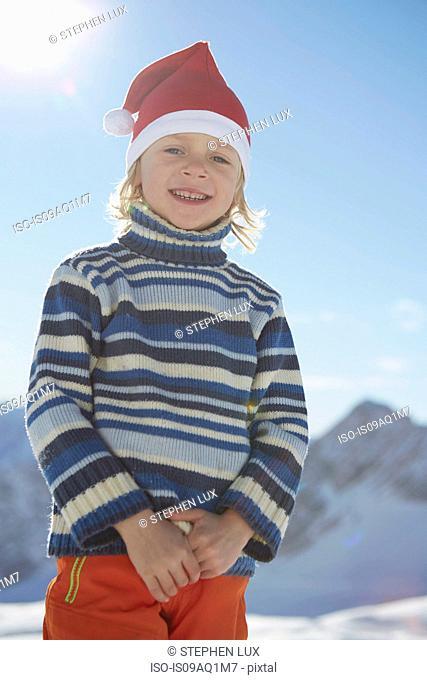 Portrait of young boy in snowy landscape, wearing Santa hat