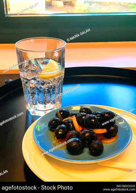 Glass of sparkling water with black olives