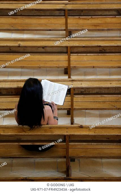 Woman reading the bible in a church