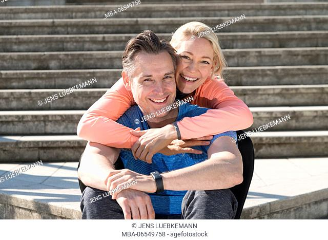 Couple in sportswear sitting on stairs, embracing, smiling, looking at camera