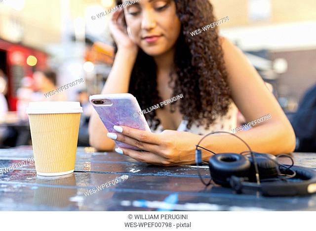 Young woman sitting at a table looking at cell phone