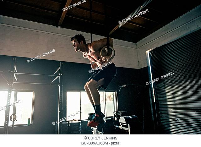 Man poised on exercise rings in gym