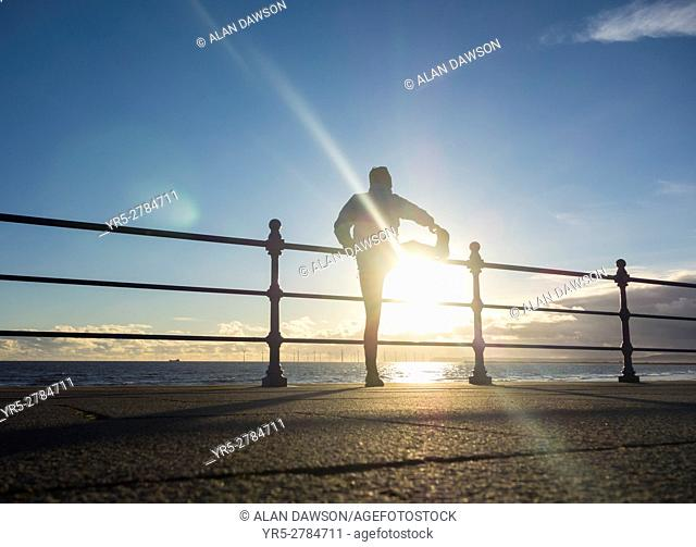 Seaton Carew, north east England, United Kingdom Jogger stretching at sunrise on a bright and cold winter morning at Seaton Carew on the north east coast of...
