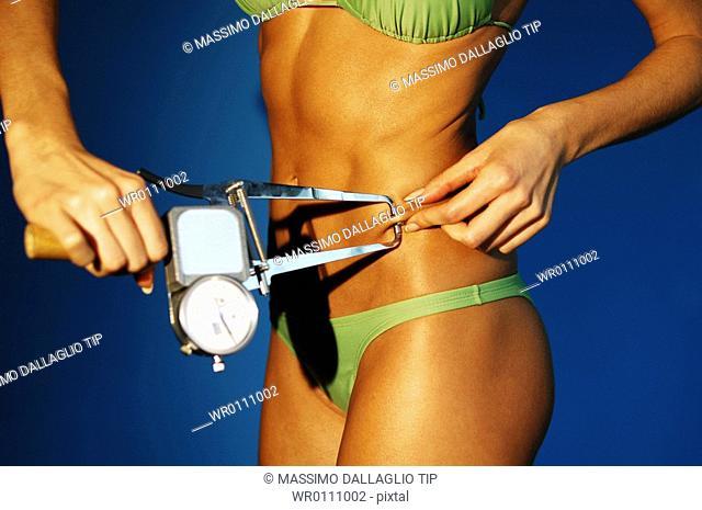 Woman measuring body fat with a caliper