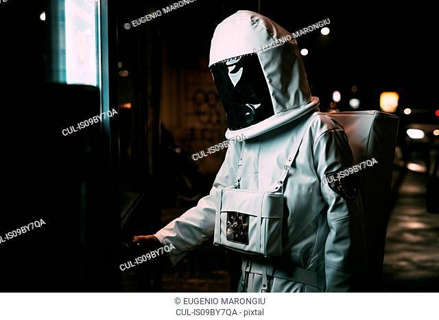 Astronaut opening door to shop at night