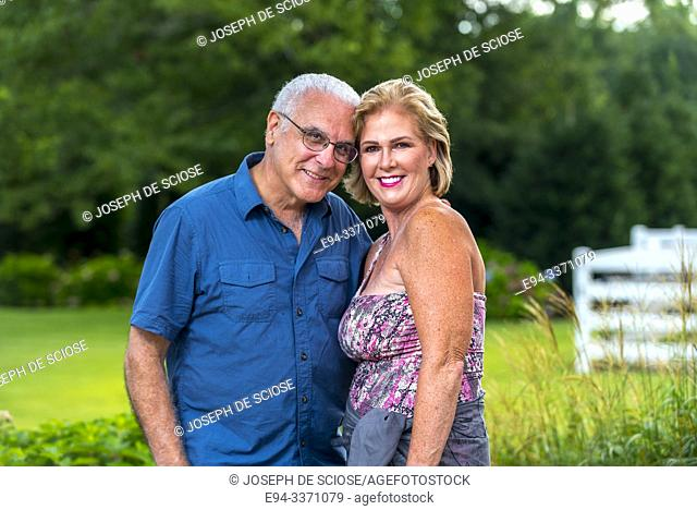 A happy 60 Year old blond woman and a 66 year old man smiling at the camera, outdoors