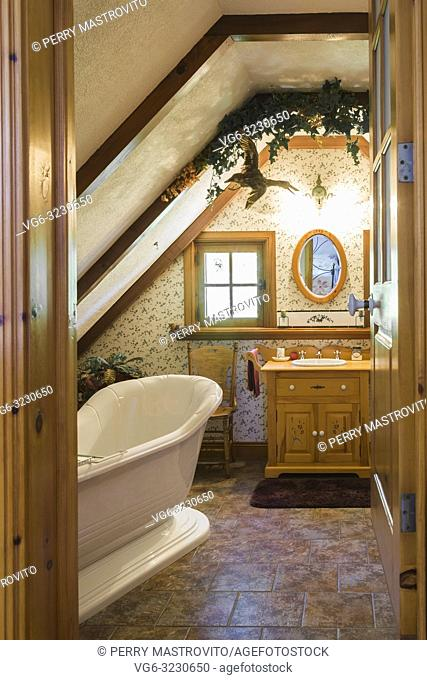 Freestanding Alcove bathtub and wooden vanity in en suite on upstairs floor inside an old 1927 Canadiana cottage style home