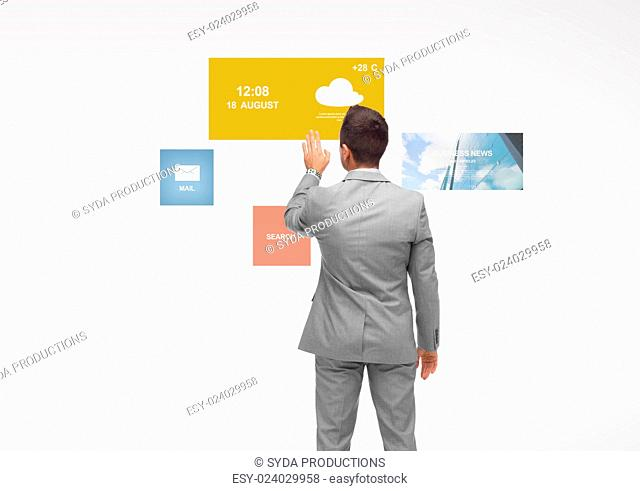 business, people, multimedia and technology concept - businessman touching virtual projection from back