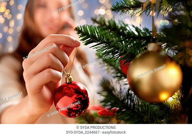 happy young woman decorating christmas tree