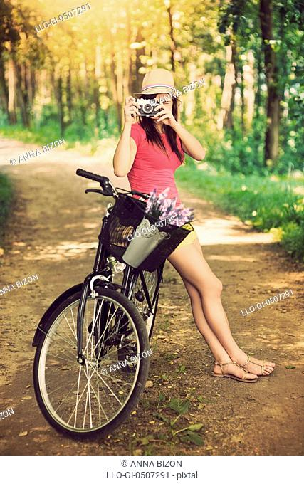 Young woman on bike photographing nature, Debica, Poland