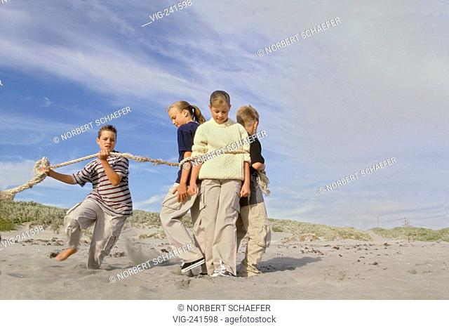 beachscene, portrait, 2 blond girls and 1 boy in the age of 10-12 years are tied up with a thick rope by a second boy  - GERMANY, 22/04/2004