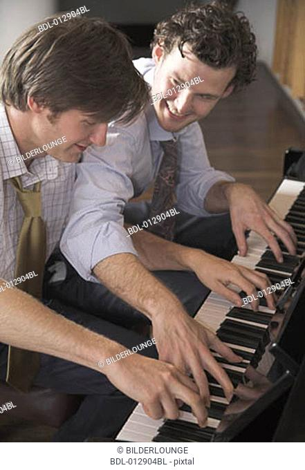 two good friends playing four handed piano