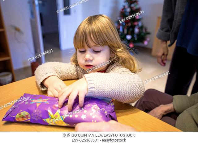 three years old caucasian blonde child with family looking to open gift, wrapped in paper, with christmas tree behind
