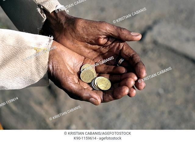 Close-up of the open hands of a beggar holding Birr coins, Addis Ababa, Ethiopia, East Africa