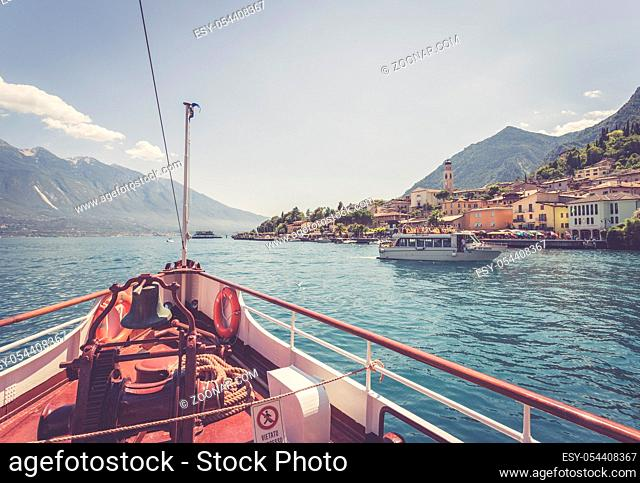 Bow of a boat on a boat tour. Blue water, moutnain range and little village, Lago di Garda, Italy