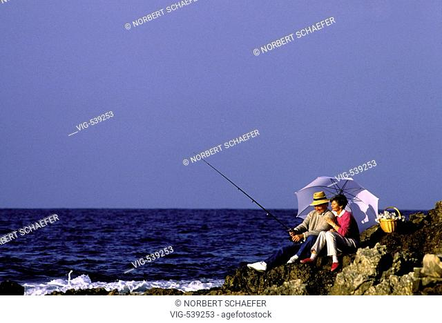 Elderly couple sitting on a rock and fishing. - 01/07/2007
