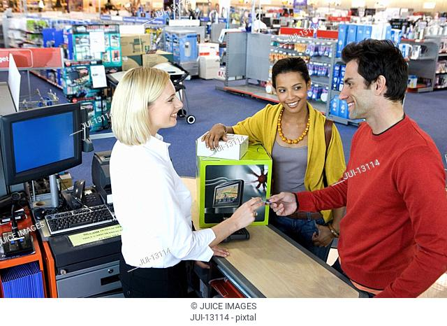 Young couple buying computer, smiling, elevated view