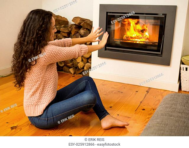 Beautiful woman warming hands on the fireplace